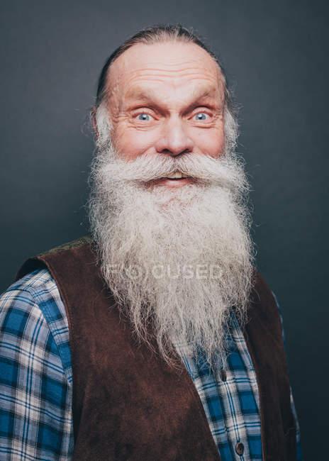 Ritratto di uomo anziano sorridente con lunga barba bianca su sfondo grigio — Foto stock