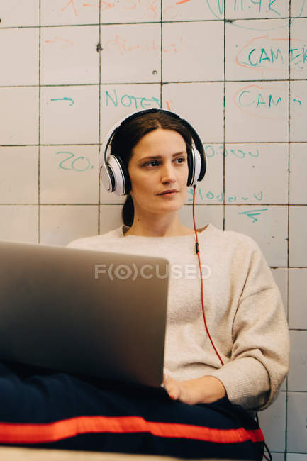Young female computer hacker listening through headphones while sitting with laptop against tile wall at creative office — Stock Photo