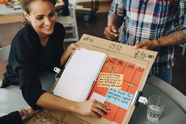 Hochwinkelaufnahme einer lächelnden Geschäftsfrau, die dem Manager am Tisch im Kreativbüro Strategie auf einem Plakat zeigt — Stockfoto