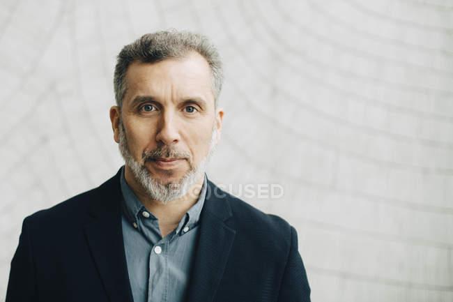 Портрет уверенного зрелого бизнесмена у стены офиса — стоковое фото