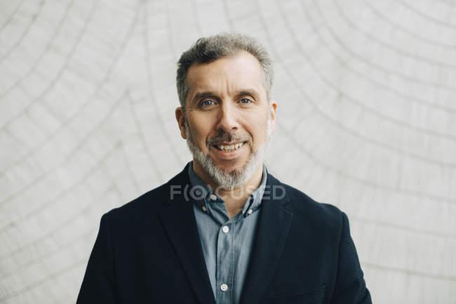 Ritratto di uomo d'affari maturo contro muro in ufficio — Foto stock