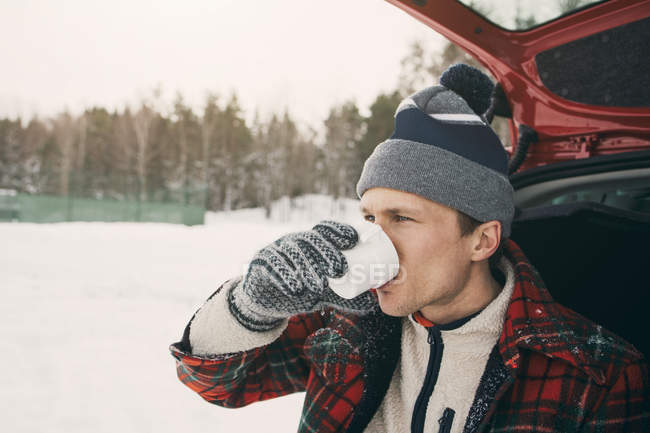 Man drinking coffee in car trunk at park during winter — Stock Photo