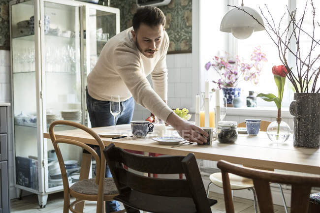 Young man arranging cup on table in kitchen at home — Stock Photo