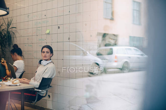 Young businesswoman looking away while sitting at desk in small office seen through window — стокове фото