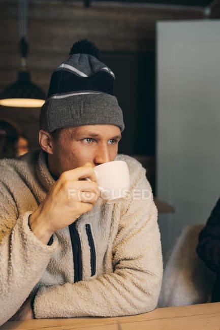 Продуманий середині дорослої людини за кавою в таблиці в бревенчатом будиночку — стокове фото