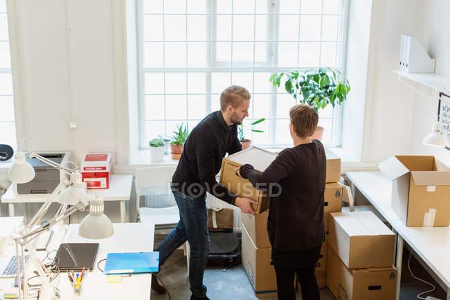 Vue grand angle des collègues d'affaires empilant des boîtes en carton par fenêtre dans un bureau créatif — Photo de stock