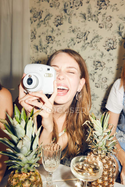 Cheerful young woman photographing while sitting amidst female friends at home during dinner party — Stock Photo