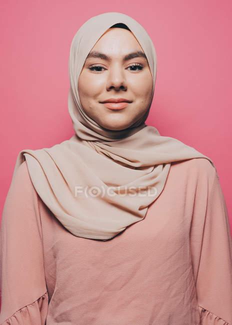 Портрет улыбающийся молодой женщины в хиджабе розовый фоне — стоковое фото