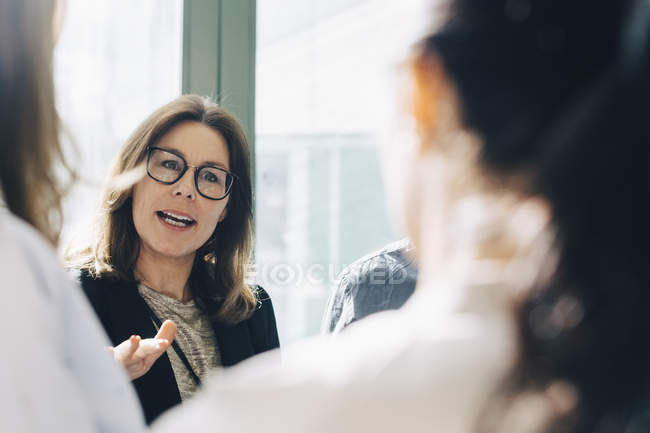 Businesswoman sharing ideas with colleagues during meeting — Stock Photo