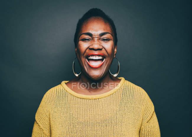 Середине взрослая женщина, смеясь над серый фон — стоковое фото