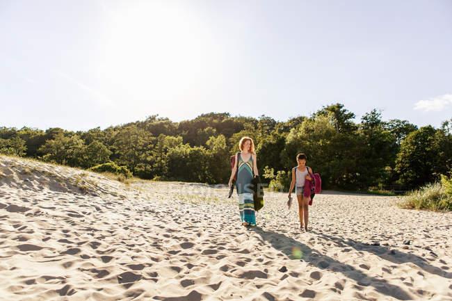 Mutter und Tochter gehen bei Sonnenuntergang auf Sand am Strand gegen den Himmel — Stockfoto