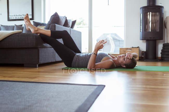 Mulher cansada, usando telefone celular enquanto estava deitado na esteira de exercícios na sala de estar — Fotografia de Stock