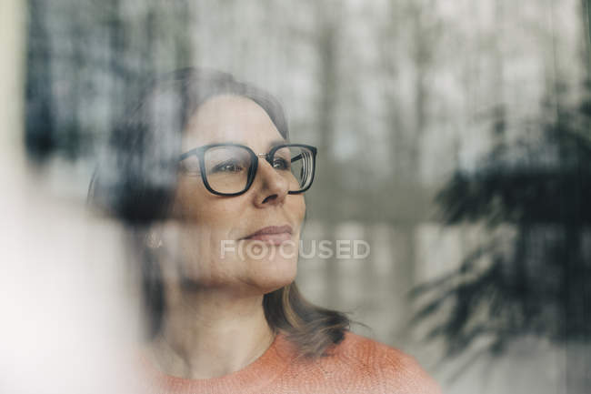 Close-up of thoughtful businesswoman wearing eyeglasses seen through window — Stock Photo