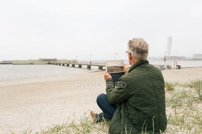 Rear view of senior male commuter photographing sea while sitting on sand at beach against clear sky — Stock Photo