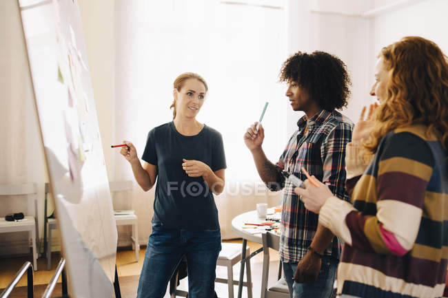 Confident businesswoman discussing project over whiteboard with technicians at creative office — Stockfoto