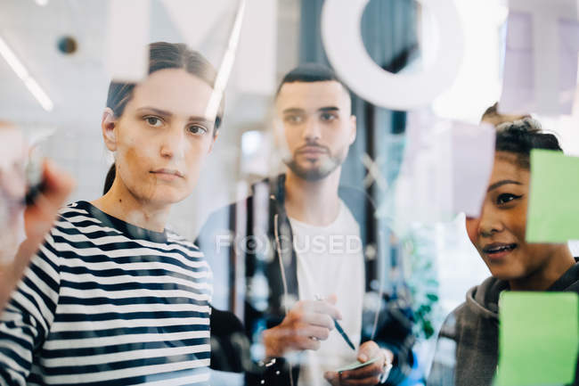 Young multi-ethnic hackers discussing strategy over glass during meeting at creative office — Stock Photo