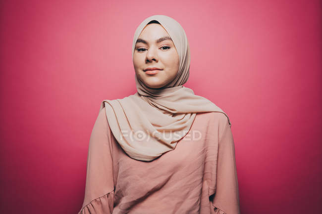 Портрет уверенно молодая женщина в хиджабе розовый фоне — стоковое фото