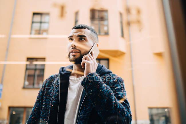 Vista a basso angolo di fiducioso giovane uomo d'affari che parla su smartphone visto attraverso la finestra — Foto stock