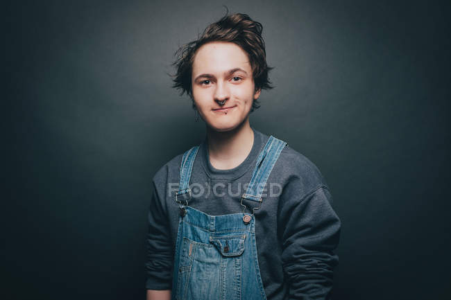 Portrait of smiling young man wearing denim overalls over gray background — Stock Photo