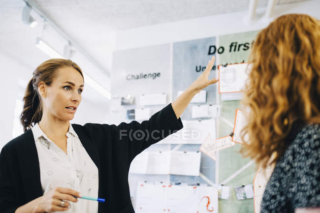 Confident female entrepreneurs discussing over strategy at creative office — Stock Photo