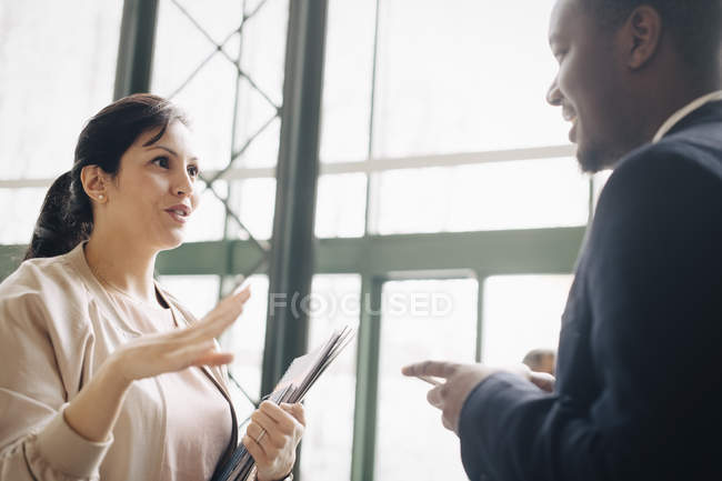 Businesswoman sharing ideas with male coworker in meeting at office — Stock Photo