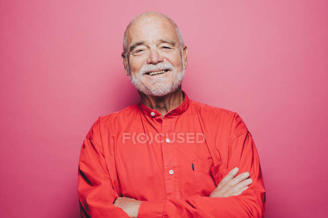 Portrait of smiling senior man with arms crossed against pink background — Stock Photo