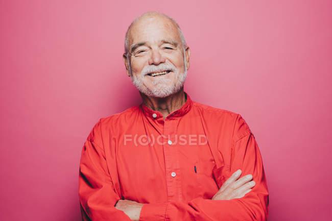 Retrato de sorrindo sênior homem com os braços cruzados contra o fundo rosa — Fotografia de Stock