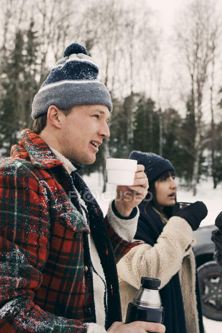 Smiling man standing with friend and having coffee during winter — Stock Photo