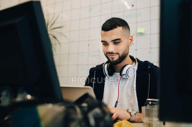 Confident young male computer hacker programming on laptop at creative office — Stock Photo