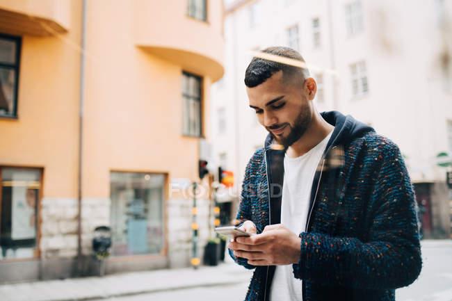 Giovane uomo d'affari fiducioso messaggistica di testo su smartphone visto attraverso la finestra — Foto stock