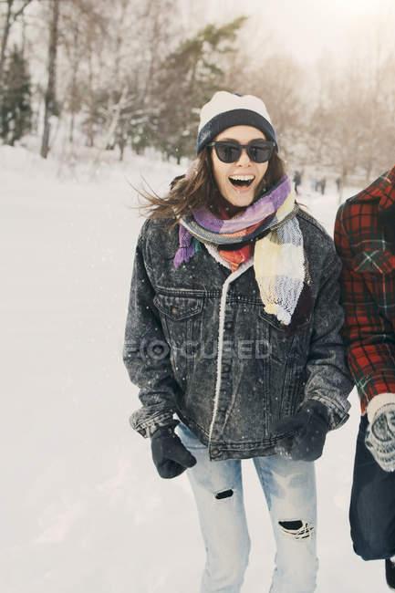 Fröhliche Frau steht mit Freund auf schneebedeckter Landschaft — Stockfoto