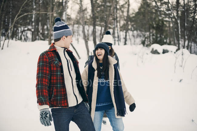 Happy friends talking while walking on snow covered field — Stock Photo