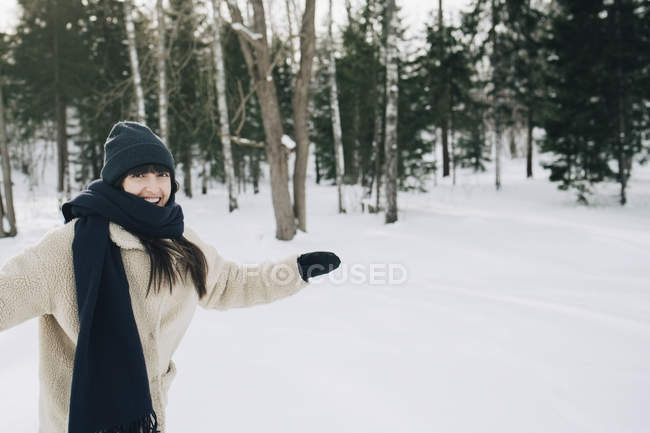 Portrait of happy woman standing with arms outstretched on snow covered landscape — Stock Photo