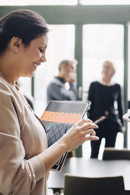 Donna d'affari sorridente utilizzando il telefono con i colleghi in background — Foto stock