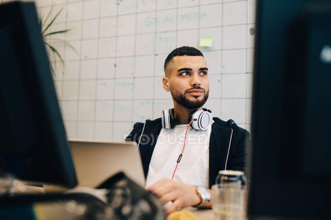 Young male computer hacker sitting with laptop while looking away at creative office — Stock Photo