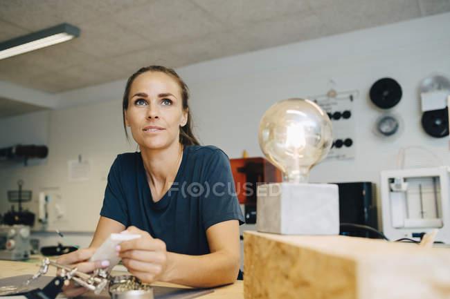 Nachdenkliche Technikerin schaut weg, während sie an der Werkbank im kreativen Büro sitzt — Stockfoto