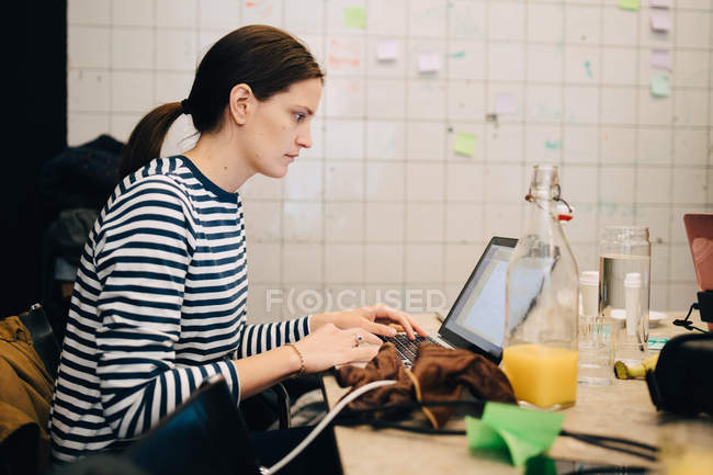 Side view of young businesswoman encrypting on laptop while sitting at desk in small office — Stock Photo