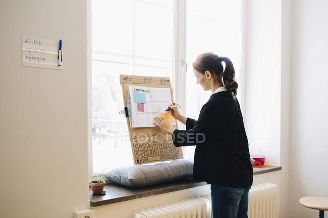 Selbstbewusste Geschäftsfrau schreibt Strategie auf Plakat über Fensterbank im Kreativbüro — Stockfoto