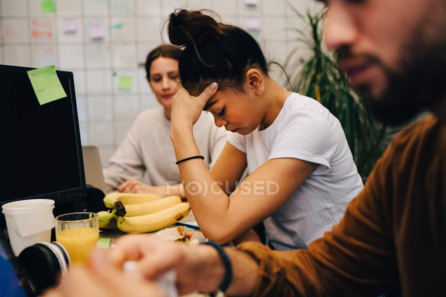 Worried businesswoman sitting amidst colleagues at desk in creative office — Stock Photo
