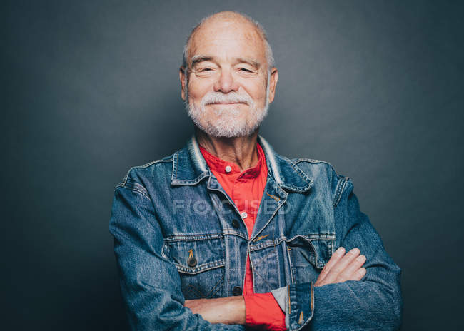 Portrait of smiling senior man with arms crossed against gray background — Stock Photo