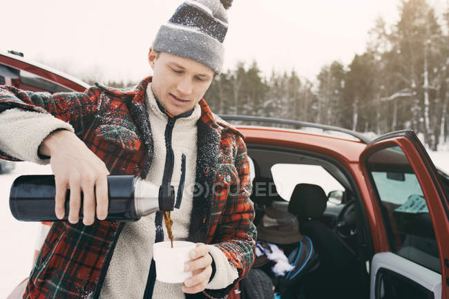 Mid adult man pouring coffee from insulated drink container while standing by car — Stock Photo