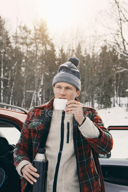 Man drinking coffee from insulated drink container while standing by car at park — Stock Photo