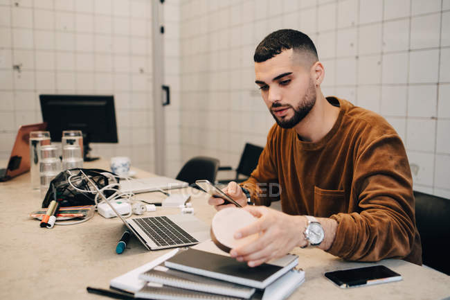 Young male hacker using smart phone while holding equipment at desk in small creative office — Stock Photo