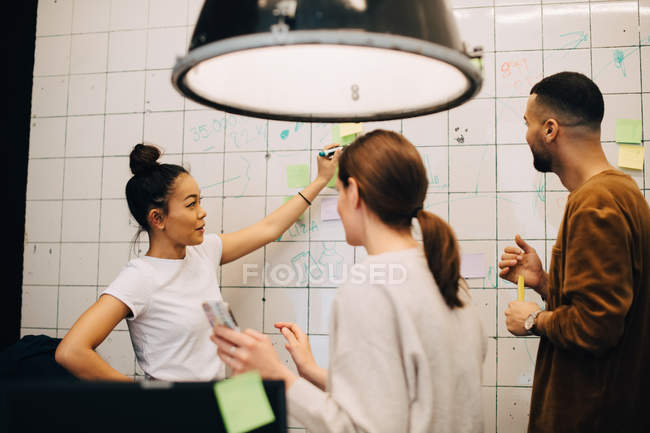 Young multi-ethnic hackers discussing strategy on wall at small creative office — Stock Photo