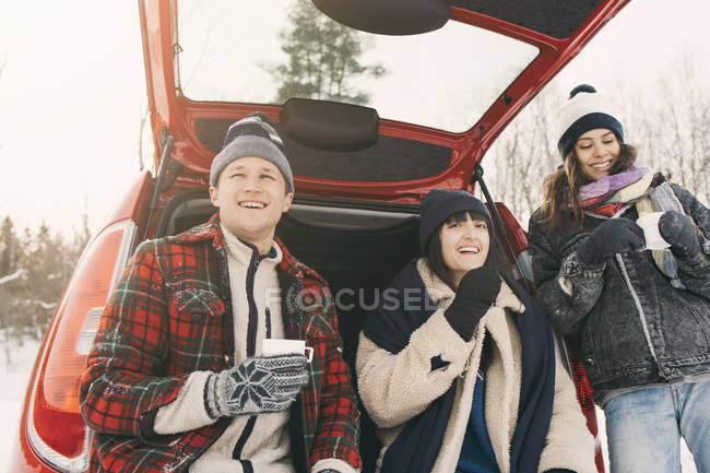 Low angle view of happy friends having coffee while resting in car trunk during winter — Stock Photo