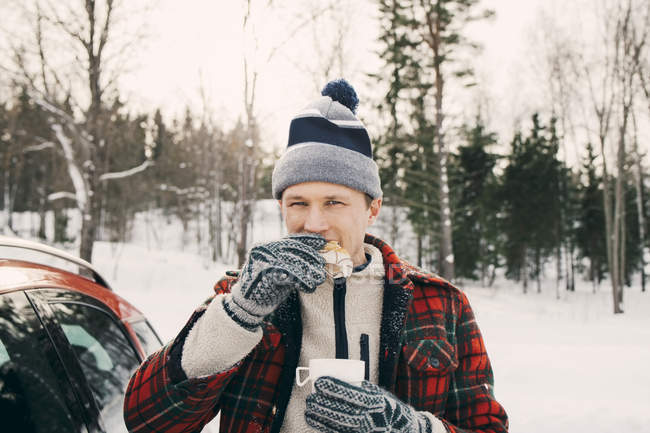 Man eating bread while having coffee in car trunk at park during winter — Stock Photo