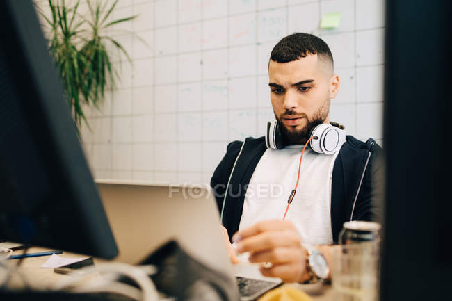Young male computer programmer coding on laptop at creative office — Stock Photo