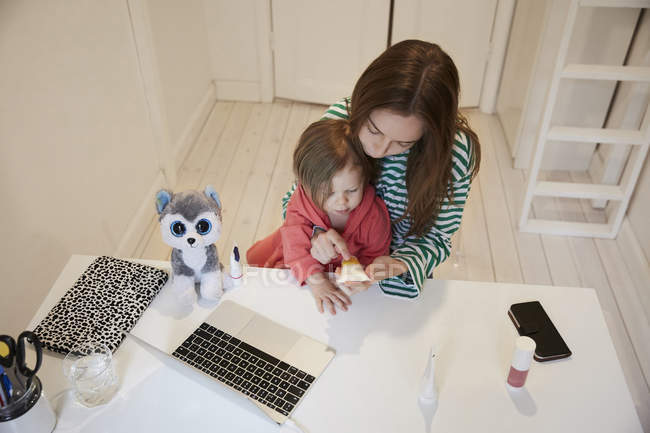 Висока кут зору blogger проведення краси продукт сидячи за столом дочка — стокове фото