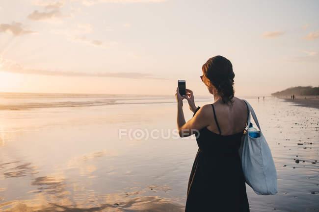 Заднього виду жінки фотографування захід сонця над морем за допомогою мобільного телефону на пляжі — стокове фото