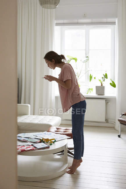 Full length side view of fashion designer photographing fabric at home — Stock Photo